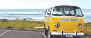 yellow vintage van parked on a parking lot in front of the beach portfolio