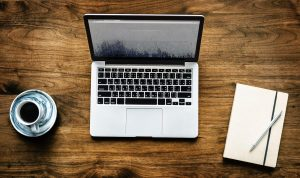 a wooden table is composed by a mac laptop, a white notebook with a pen as well as with a cup of coffee services