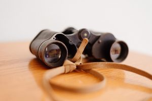 vintage binoculars placed on top of a wooden table services