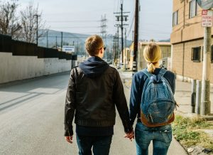 young couple in relationships holding hands walking on the street with a backpack