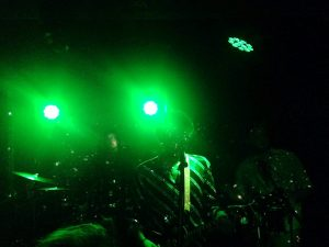 LaGardère live concert at Sabotage, with the vocalist and the drummer playing in a dark greenish setting