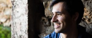 young man smiling and looking to the side inside a stone house Tomás VP Storyteller
