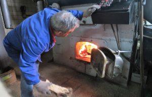 craftsman working for the best coffee roaster using firewood oven inside flor da selva factory in lisbon, portugal - portfolio