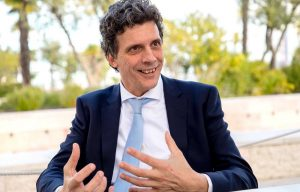 professor in a suit and tie smiling and sharing his thoughts on the business culture in portugal - portfolio