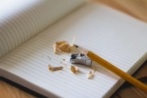 an empty notebook placed in a wooden table with an orange pencil and a pencil sharpener services