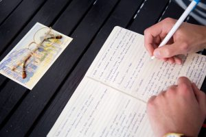 a person is writing on a notebook with a white and blue pen and a postcard stands on top of the table along with glasses services
