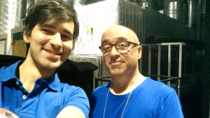 Two men dressed in blue taking a picture in the backstage of a television studio with a piano