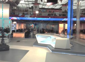 tv studio with a table and chair and video equipment